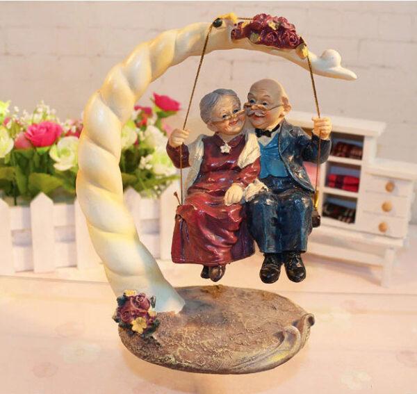 Figura decorativa de abuelos en columpio